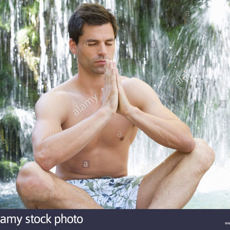 a-man-meditating-by-a-waterfall-B07M6C